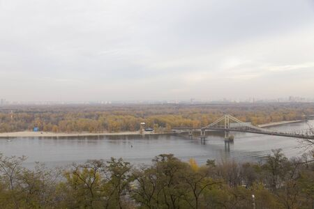 Panoramic view of the city of Kiev. Footbridge and autumn park.