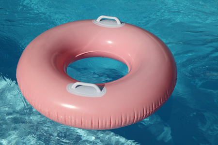 rubber ring: Pink rubber ring on the blue pool. Stock Photo