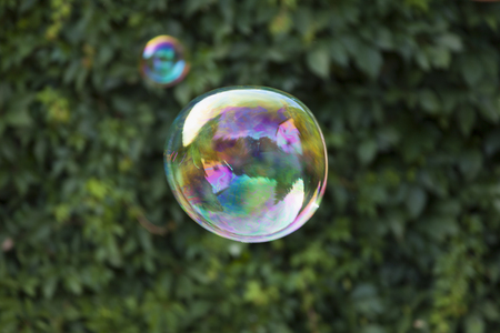 whiff: Rainbow soap bubble irregular shape on green blurred background. Stock Photo