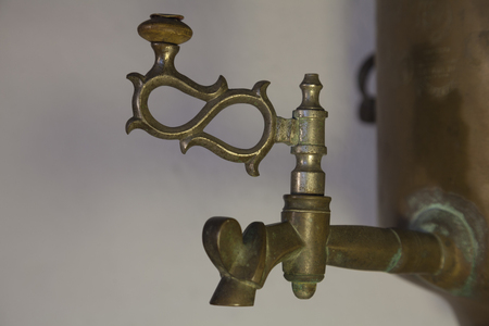 pitting: Old brass faucet of antique samovar on background white wall. Stock Photo