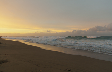 warm climate: Dramatic colors of sunset after a tropical rainstorm. Strong waves on the ocean after the storm.