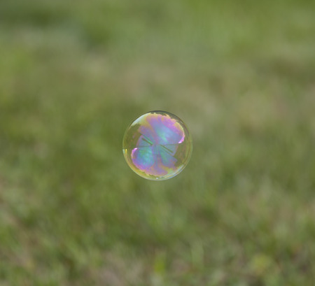 whiff: Rainbow soap bubble on green blurred background. Stock Photo
