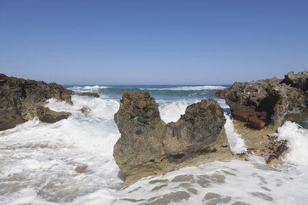 sputter: Blue sky, blue sea and rocks. Waves, surf and white sea foam.