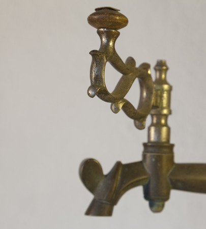 corrode: Old brass faucet of antique samovar on background white wall. Stock Photo