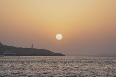 warm climate: The ball of the sun at dawn emerges from the horizon. After hill is the lighthouse. Nature meets a hot summer day.