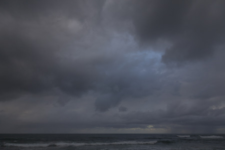 lumen: Thunderstorm under sea. Heavy gray storm clouds. In the lumen of the blue sky with clouds. Light of sunset in the distance.