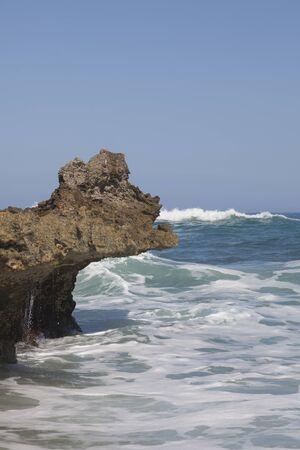 sputter: Blue sky, blue sea and surf. Waves, rocks and white sea foam.