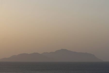 warm climate: Island in the sea at dawn misty haze. Stock Photo