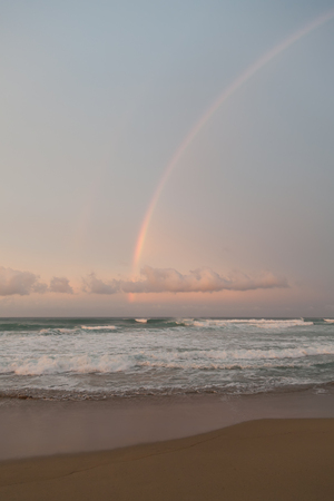 warm climate: Rainbow, pink colors of clouds and sea foam on waves. Big surf waves. Stock Photo