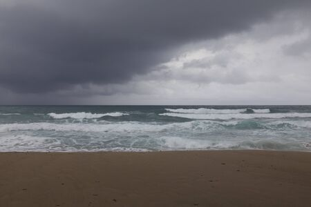 windstorm: Thunderstorm under sea and waves, white clouds and sea foam, dark yellow sand beach.