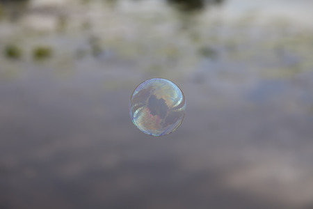 whiff: Rainbow soap bubble on the background reflections in the river. The sky with clouds and aquatic plants.