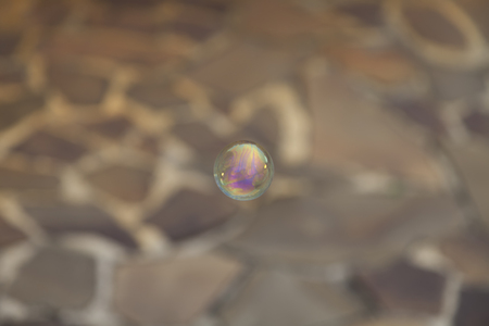 whiff: Rainbow soap bubble on blurred background. Stock Photo