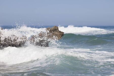 sputter: Blue sky, blue sea and waves, breaking on rocks. Surf and white sea foam.