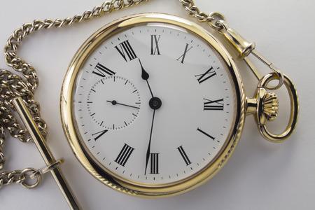 numeros romanos: Relojes de metal amarillo con números romanos negros sobre un fondo blanco. Foto de archivo