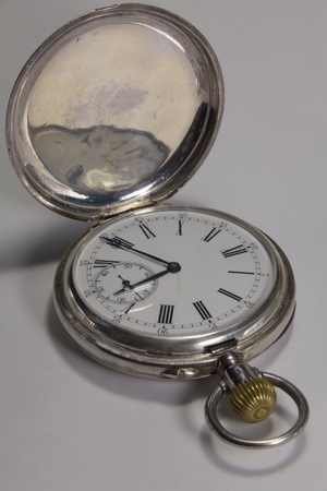 horologe: Antique watches made of silver metal with black Roman numerals on a white background.