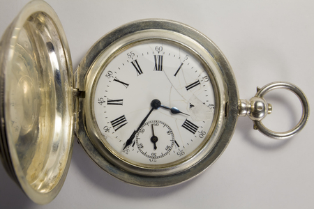 chainlet: Antique watches made of silver metal with black Roman numerals on a white background. The dial is partially damaged.