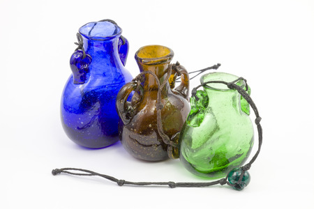 tabernacle: Glass jars of different colors on a white background. Vintage banks. Extremely bright light. Beads different-shaped glass on a shoestrings.