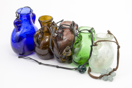 shoestrings: Glass jars of different colors on a white background. Vintage banks. Extremely bright light. Beads different-shaped glass on a shoestrings.