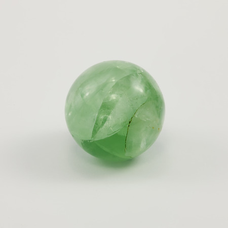 fluorite: A small ball of fluorite, gemstone green color on a white background. Stock Photo