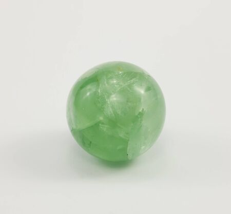 green gemstone: A small ball of fluorite, gemstone green color on a white background. Stock Photo