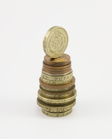 britannia: Column of coins with one pound on the top in the form of a Christmas tree on a white background. Stock Photo
