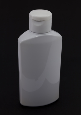 White plastic jar on a dark background. Medical plastic jar of shampoo.