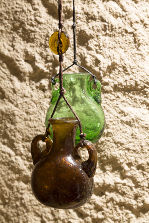 shoestring: Jars of dark and green glass on the background of a concrete wall. Vintage bank. Extremely light. Bead glass on a shoestring. Stock Photo