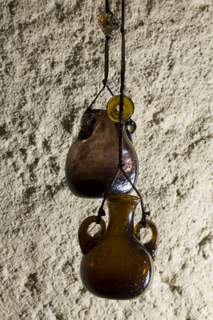 shoestring: Jars of dark glass on the background of a concrete wall. Vintage bank. Extremely light. Bead glass on a shoestring.