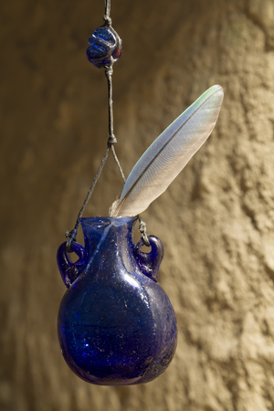 shoestring: Jar of blue glass on the background of a concrete wall. Vintage bank. Extremely light. Feather bird with blue, green and gray color. Bead glass on a shoestring.