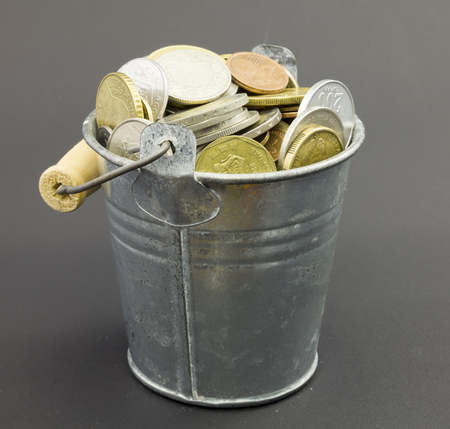 bucket of money: Natural little old metal bucket with coins on a dark background. Stock Photo