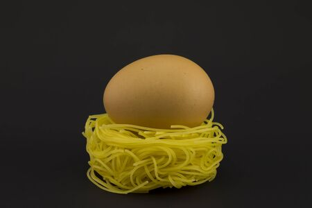 paschal: Thin pasta in a form of nest with chicken egg on a dark background. Stock Photo