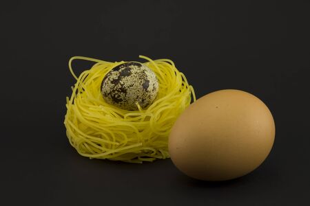 paschal: Thin pasta in a form of nest with quail and chicken eggs on a dark background. Clarity on quail egg.