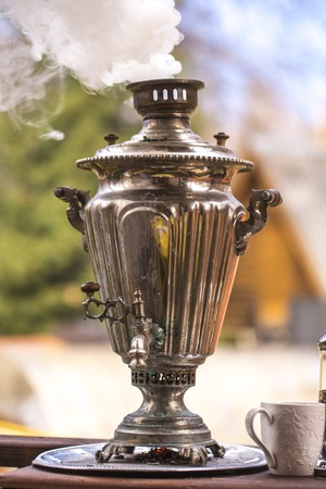 kettle on firewood in Russian traditions. Samovar. Stock Photo