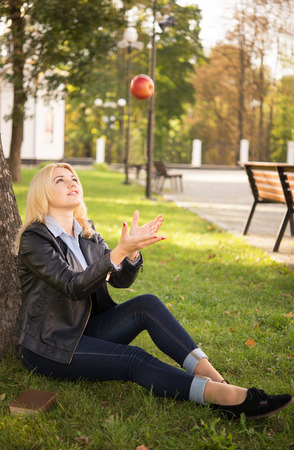 beautiful blond girl catches an apple near the tree photo