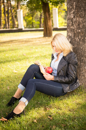 beautiful blond girl sitting under a tree and reading a book photo