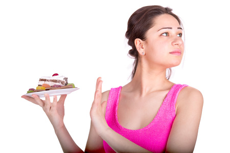 unhealthy diet: beautiful sports girl refuses sweets