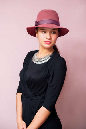 looking aside: beautiful girl in a hat on a pink background looking aside