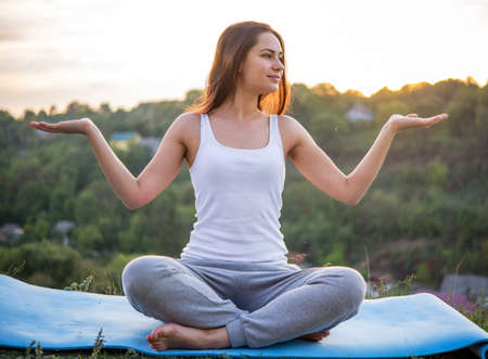 spreading arms: beautiful young girl meditating at sunset sitting spreading arms Stock Photo