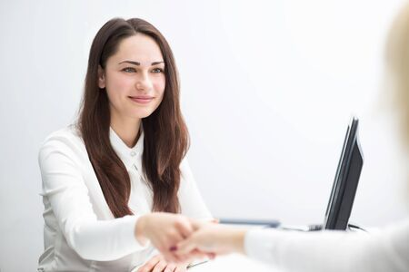 concludes: beautiful young business woman in the office concludes contract