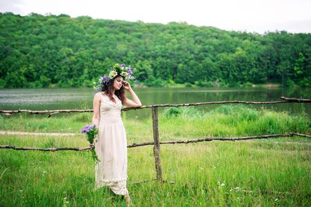 dreamy girl in a wreath and with a bouquet of flowers near the river