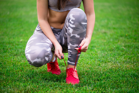 young girl athlete tying shoes before exercise closeup