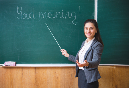 A young smiling teacher explains near the board