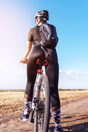 pretty sport girl on a mountain bike in the field rear view close up