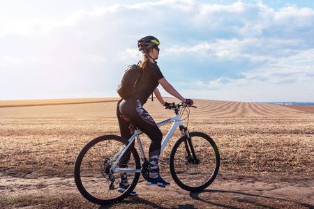 sport girl on a mountain bike on a background of a sunny field