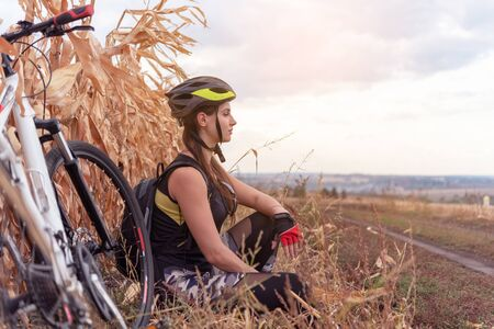young cyclist woman resting sitting in a field near the road Reklamní fotografie