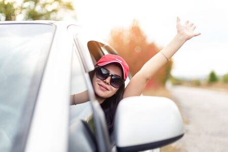 pretty girl in cap and sunglasses waving hand while driving