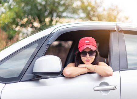 pretty girl in a cap and sunglasses rests on the open drivers window
