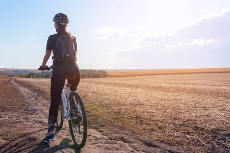 girl on a mountain bike rides on the evening field road Reklamní fotografie