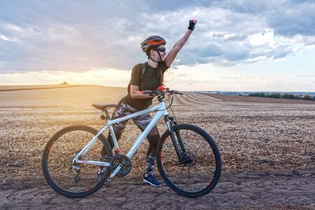 Young pretty smiling cyclist conquers the field route Stok Fotoğraf
