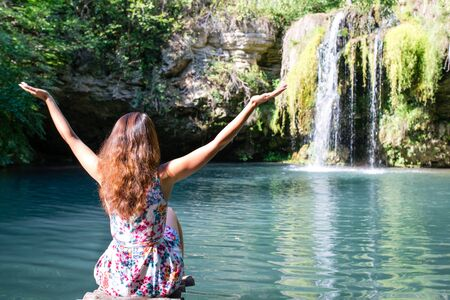 girl in dress sitting in front of a waterfall with arms outstretched Stok Fotoğraf